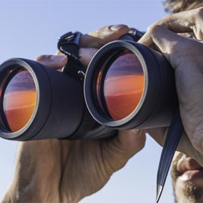 Close up of a man looking through binoculars