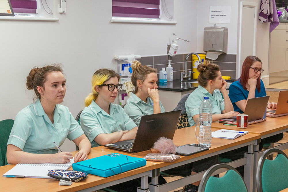 Veterinary nurse students studying with laptops